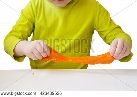 Close-up Of Orange Slime In Childrens Hands. Hands Stretch The Slime. Concept - Childrens Educationa