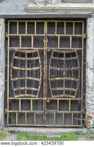 Old Doorway With A Rusty Metal Barred Door In The Shape Of Wine Barrels. Padlocked And Abandoned.