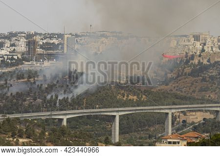 Jerusalem, Israel - June 10th, 2021: A Fire Fighting Airplane Releasing Fire Retardant Over A Forest