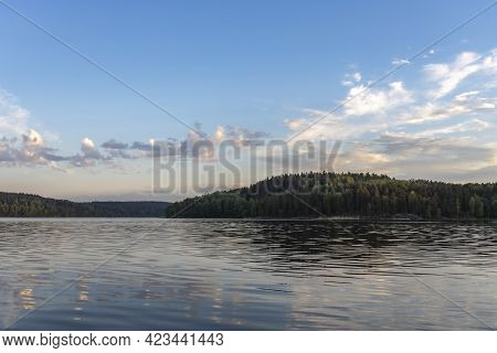 Evening Landscape With A Lake. The Forest Is Illuminated By The Rays Of The Setting Sun. The Sky And