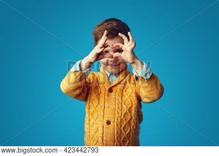 Cute Lovely Kid Wearing Yellow Cardigan, Showing A Heart Shape With Hands