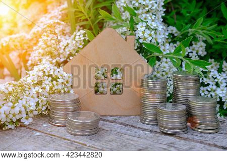 A Small Wooden Model Of A House Among Blooming White Flowers Of Greenery And Stacks Of Coins. Concep