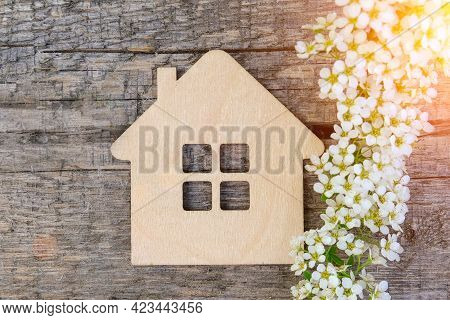 Mock-up Of A Wooden House On A Wooden Background, Close-up. Nearby Is A White Branch Of Flowers. Rea