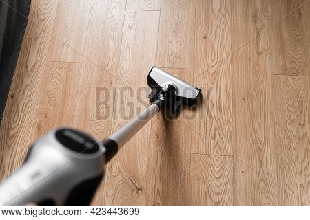 Cleaning Wooden Floor With Wireless Vacuum Cleaner. Handheld Cordless Cleaner. Household Appliance.