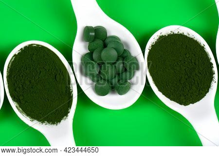 Chlorella Or Spirulina In The Form Of Tablets And Powder On A Green Background, Close Up.