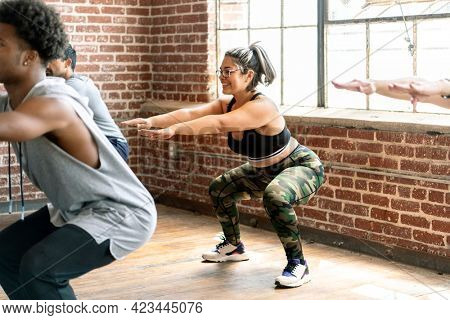 People doing squats in fitness class
