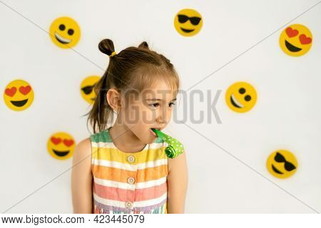 World Smile Day. Anthropomorphic Smile Face. A Little Girl On A White Background With Emojis Of Vari