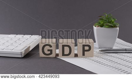 Concept Word Gdp, Gross Domestic Product On The Wooden Blocks On Gray Background From Green Flower A