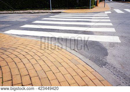 Crosswalk. White pedestrian crossing marking on road surface.