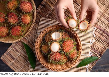 Woman Hand Holding And Eating Ripe Rambutan Fruit In A Basket, Rambutan Is Tropical Fruit And Native