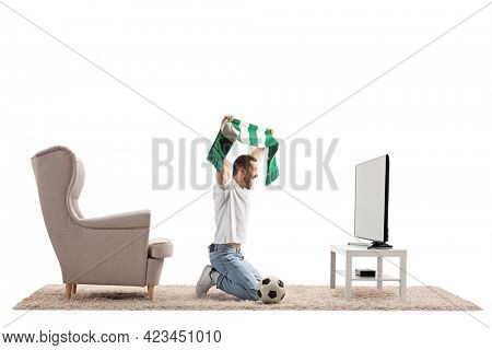 Young man kneeling in front of a tv and cheering with a scarf and a football isolated on white background