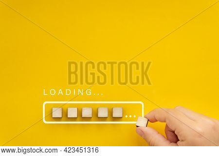Loading, Hand Putting Wood Cube In Progress Bar. Loading Bar On Bright Yellow Background