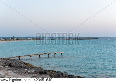 Pier In Deserted Beach Of Ses Illetes On The Island Of Formentera In Spain.