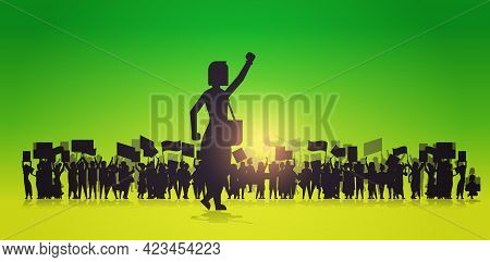 Silhouette Of Woman Raising Hand Over Crowd Protesters Holding Protest Posters Men Women With Blank