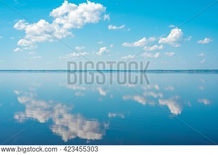 Cloudscape. Clouds In Blue Sky And Reflection In A Large Lake. White Cumulus Clouds In Sky Over Blue