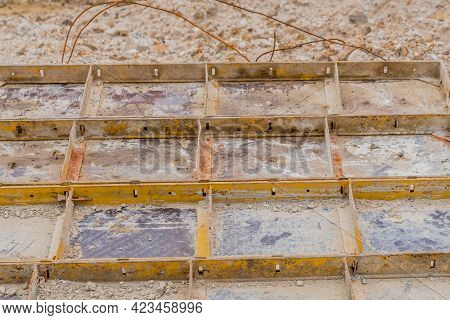 Metal Masonry Forms Laying In Dirt At Construction Site.
