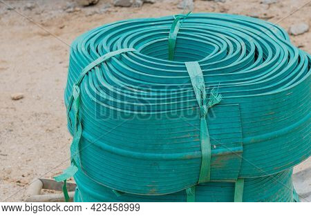 Wide Grooved Rubber Strips Rolled Up At New Construction Site.