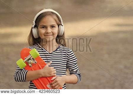 Enjoy Your Vacation. Happy Child Hold Penny Board Outdoors. Enjoying Music And Skateboarding. Skate