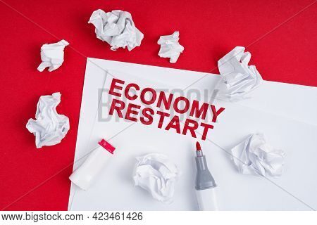Business And Finance Concept. On A Red Background Lies Crumpled Paper, A Marker And A Sheet Of Paper