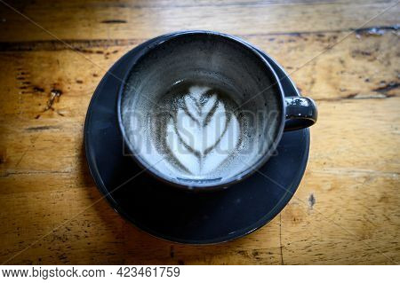 A Cup Of Goth Latte Or Charcoal Latte On Wooden Table (focus On Coffee Surface). The Black Colour Is