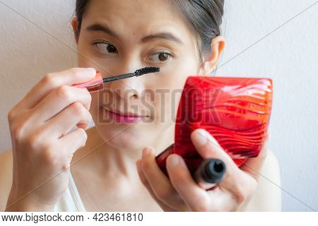 Close Up Of Young Asian Woman Holding Mini Mirror And Applying Black Mascara On Her Eyelashes With M