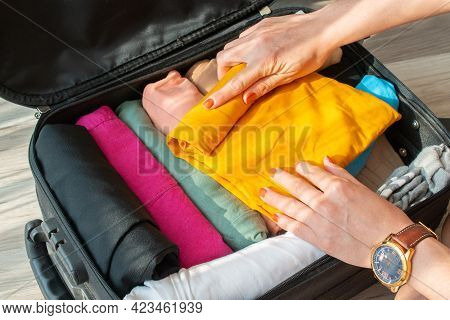 Close Up Of Tourist Woman Open Suitcase For Pack And Arranging Colorful Cloths For Travelling. Conce