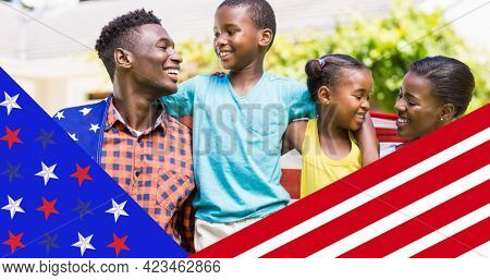 American flag design against african american family wrapped in american flag smiling. american independence day celebration concept
