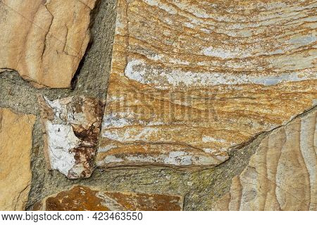 Stone Wall With Layered Flaky Peeling Rocks Close Up. Natural Abstract Background