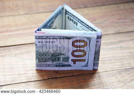Hundred Dollar Notes On Wooden Boards. Hundred Dollar Bills Folded In Triangular Shape. Money In Cas
