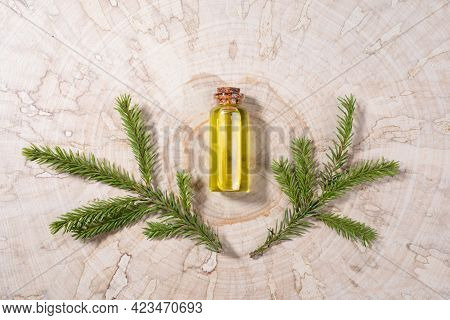 Small Glass Bottle With Coniferous Spa Aromatic Essential Spruce Oil And Two Small Branches On Woode