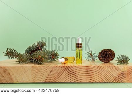 Composition With Of Essential Spruce Oil In Small Glass Bottles, Twigs, Cone On Wooden Stand On Ligh