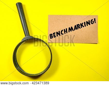 Business Concept.text Benchmarking On Brown Card With Magnifying Glass On Yellow Background.