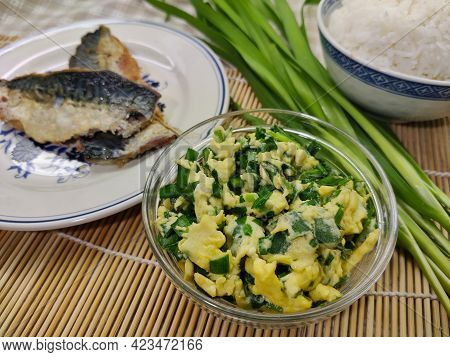 Scrambled Eggs With Spring Onion In Transparent Bowl. There Are Two Fish Fillets On The Left Side An