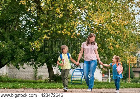 Woman And Two Children From Back. Mother Accompanies The Students Along Way. Children With Briefcase