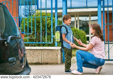 Mother Accompanies The Child To School. Mom Encourages The Student To Accompany Him To School.caring