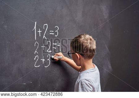 Primary Education. Side View Student Solves Math Example On A Blackboard In Math Class. An Elementar