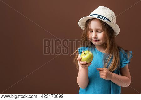 Portrait Of A Cute Little Girl Holding An Apple On A Brown Background. The Child Wears A Straw Hat A