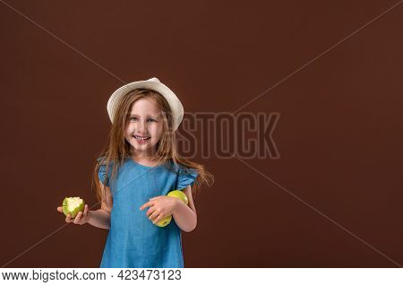 Portrait Of A Cute Little Baby Girl Holding An Apple On A Brown Background. The Child Is Wearing A S