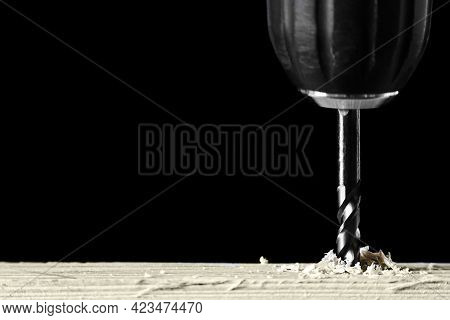 Electric Drill Bit Drills Hole In Board Close-up Isolated On Black With Copy Space. Concept Of Const