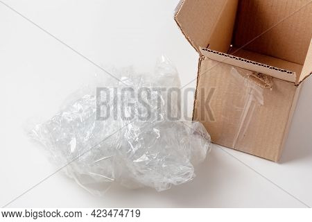 A Lump Of Crumpled Cellophane Packing Filler Next To An Open Cardboard Box. Safety Of Parcels And Th