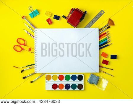 School Album With School Supplies On Yellow Background. In Center, On Black Surface, Is An Album, Pl