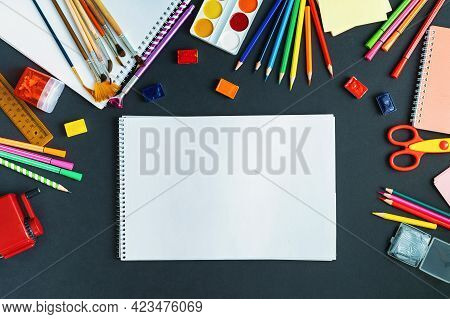 School Supplies Displayed On Black Board Background. In Center, On A Black Surface, Is An Album, A P