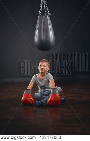 Schoolboy Boxer, Dressed In Casual Clothes And Boxing Gloves, Looks At A Punching Bag And Shows A Bo