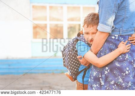 Happy Mother And Son Family. A Boy Hugs His Mother, An Elementary School Student. A Woman Meets A Ch