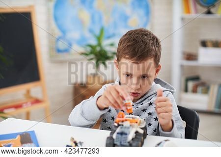 Cute Seven-year-old Boy, A Schoolboy, Has Fun With The Constructor, Sitting At The Table, Instead Of
