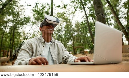 Smiling Young African American Man Sitting In Virtual Reality Glasses Near Laptop In Spring Nature,