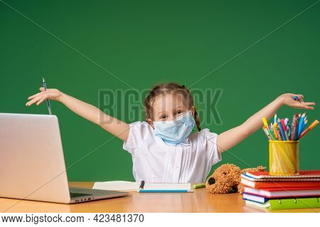 Cute Little Girl In A Mask, Uses A Laptop To Study On Internet, Does Homework On Distance Learning D