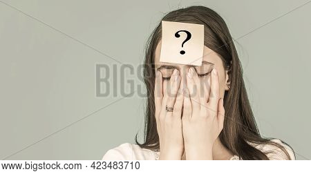 Confused Female Thinking With Question Mark On Sticky Note On Forehead. Rying Woman With Question Ma
