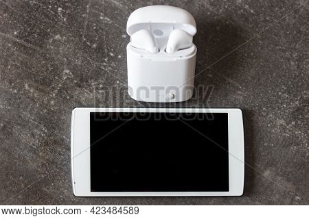White Smartphone And Wireless Headphones In A Charging Container On A Dark Background, Modern Techno