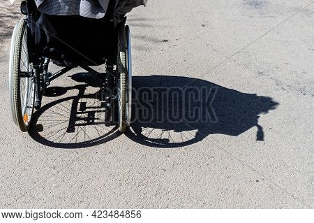 Shadow Of A Person In The Wheelchair Is Shadowed To Right. Shadow Of A Woman With A Disability Sitti